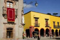 Mexico, Bajio, San Miguel de Allende, El Jardin, Part view of Museo Casa de Allende and yellow painted arcades, people and fruit juice vendor.
