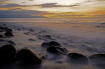 Mexico, Jalisco, Puerto Vallarta, Waves and rocks on beach at sunset.