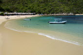 Mexico, Oaxaca, Huatulco, Playa La Entrega, Stretch of sandy beach lined with thatched open fronted restaurants, with tour boat in shallow water in foreground.