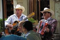 Mexico, Bajio, Guanajuato, Mariachi musicians playing at cafe in Jardin de la Union.