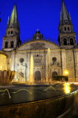 Mexico, Jalisco, Guadalajara, Fountain in foreground of cathedral exterior facade and bell towers at night in Plaza Guadalajara.
