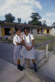 West Indies, Jamaica, Two schoolgirls in checked dresses in playground in front of school buildings.