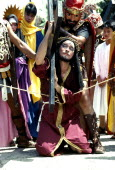 Philippines, Marinduque Island, Boac worshipper dressed as christ carrying cross during the moriones festival.