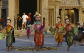Cambodia, Siem Reap, Angkor, Angkor Wat, child dancers in traditional dress with tourists framed by temple entrance behind.