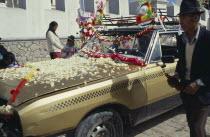 Bolivia, La Paz, Copacabana, car blessing ceremony, car with bonnet covered in flower petals.