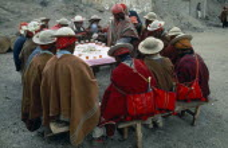 Bolivia, La Paz, Amarete, Fiesta de San Felipe held on May 1st, group of men sat around table being served hot drink.