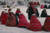 Bolivia, La Paz, Amarete, Fiesta de San Felipe held on May 1st, group of women wearing red woven shawls seated in circle.