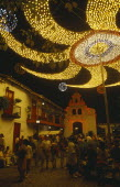 Colombia, Antioquia, Medellin, Christmas lights at Cerro Nutibara, crowds in small cobbled square under illuminated lights at night.