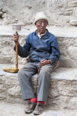 Nepal, Upper Mustang, Lo Manthang, elderly man praying with prayer wheel in the square near the king's palace.