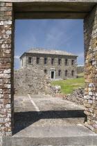 Ireland, County Cork, Kinsale,  Charles Fort  Museum building seen through the door way of a ruined building built in 1678.