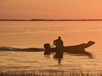 USA, Florida, Fisherman in his motorboat at Sunset.