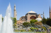 Turkey, Istanbul, Sultanahmet, Haghia Sophia with dome and minarets beyond the water fountain in the gardens with sightseeing tourists.