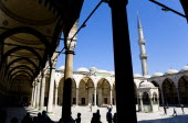 Turkey, Istanbul, Sultanahmet Camii, The Blue Mosque Courtyard and minaret with Absolutions Fountain in the middle and tourists walking in the shade under domed arches.