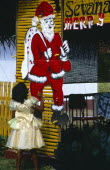 Sri Lanka, Christianity, little girl in yellow party dress looking up at large cut-out of father christmas pinned to yellow painted frame.