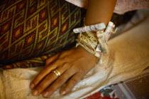 Cambodia, Buddhist wedding ceremony, money attached to wrist.