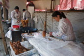 China, Jiangsu, Nanjing, Road-side bakery shop, baker cutting strips of dough that will be twisted and deep-fried in a wok to ptoduce Yu Tiao a popular breakfast bread usually eaten with warm soyamilk...