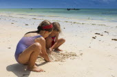 Zanzibar, Paje, Two young girls playing in the hot sunshine of the sandy beach.