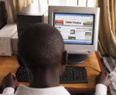 Uganda, Kabarole District, Fort Portal Teacher Training College Student teacher sat at a PC reading a National Newspaper