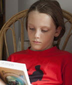 Education, 9-year old girl in vivid red t-shirt sat reading book.