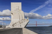 Portugal, Estremadura, Lisbon, Padrao dos Descobrimentos, Carving of Prince Henry the Navigator leading the Discoveries Monument with the Ponte 25th Abril Bridge behind.