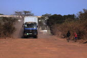 Gambia, heavy goods vehicle carrying sea container on unsurfaced red dirt road to terminal on the Bund Road.