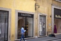 Italy, Lazio, Rome, Via del Condotti, Exterior of the Valentino designer clothing shop with woman begging outside.
