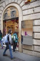 Italy, Lazio, Rome, Via del Condotti, Tourists looking at shoe display in the Jimmy Choo shop.