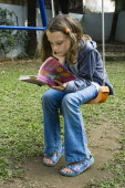Education, Reading, 10 year old girl reading on swing in garden.