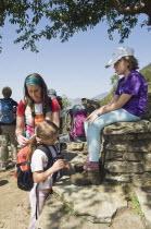 Nepal, Pokhara. Western family with children resting during trek in Nepali Himalayan hills near Pokhara.