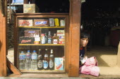 Nepal, Pokhara. Girl sat in a  shop doorway on a trekking route with western snacks for sale.