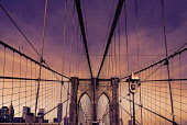 USA, New York, Brooklyn Bridge. View across bridge towards Manhattan skyline part framed by central stone tower and intersected by steel wires and suspension cables.