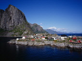 Norway, Lofoten, Moskenesoya Island, Hamnoy fishing village.  Red  white and green painted houses on rocky promontory with Festhaeltinden Mountain on left behind.