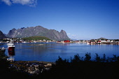 Norway, Lofoten, Moskenesoya Island, Sund fishing village.  Red and white painted houses overlooking small harbour with moored fishing boats.