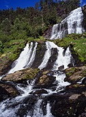 Norway, Rogaland, Svandalsfossen, Waterfall cascading over tiered rock face surrounded by trees near town of Sauda.
