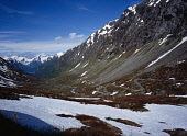 Norway, Sogn og Fjordane, Videdalen, Looking west along winding road at foot of mountains part covered with snow.