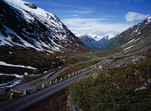 Norway, Sogn og Fjordane, Videdalen, Looking west along winding road with hairpin bend at foot of mountains part covered with snow.
