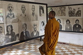 Cambodia, Phnom Penh, Buddhist monk looking a victims' photos, Toul Sleng Genocide Museum S-21. Toul Sleng was a high school, taken over by the Khmer Rouge and turned into a prison, where people were...