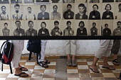 Cambodia, Phnom Penh, Western tourists lower legs and feet visible beneath a display of victims' photo portraits at Toul Sleng Genocide Museum S-21. Toul Sleng was a high school, taken over by the Khm...