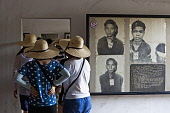 Cambodia, Phnom Penh, Tour group looking at victims' portraits, Toul Sleng Genocide Museum S-21. Toul Sleng was a high school, taken over by the Khmer Rouge and turned into a prison, where people were...
