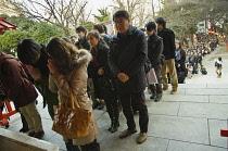 Japan, Tokyo, Shinjuku, Hanazono Jinja shrine, long line of New Years worshippers in line to worship.