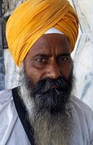 India, Delhi , Head and shoulders portrait of Sikh man wearing orange turban.