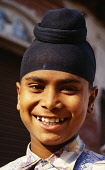 India, Rajasthan, Bharatpur , Head and shoulders portrait of smiling Sikh boy with hair tied in a topknot.