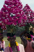 India, Kerala, Man in Festival Parade wearing large floral head dress.
