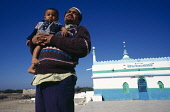 India, Gujarat, Veraval , Muslim man holding toddler with blue green and white painted mosque in background at fishing port on the south coast of Saurashtra.