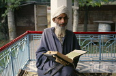 India, Kashmir, Religion, Muslim man reading from the Koran.
