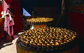 China, Tibet, Shigatse, Tashilhunpo Monastery. Large round trays of butter lamps burning with monk standing nearby.