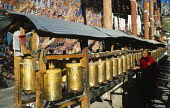 China, Tibet, Lhasa, Chagpo Ri. Painted carvings along a wall with monk spinning row of prayer wheels in front.
