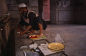 Pakistan, Punjab, Lahore, Badshahi Mosque,  Interior with Muslim pilgrim preparing meal.