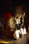 Cambodia, Siem Reap Province, Angkor Wat, Interior of shrine on the upper level with visitors lighting incense at base of Buddha figure seated below naga with multi headed hood.