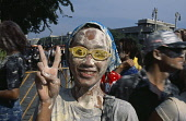 Thailand, Bangkok, Girl covered in mud  wearing goggles with fingers held in the peace sign  celebrating the Songkhran Festival. Thai New Year  15 April.